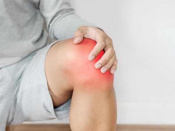 写真:膝を押さえるイメージ